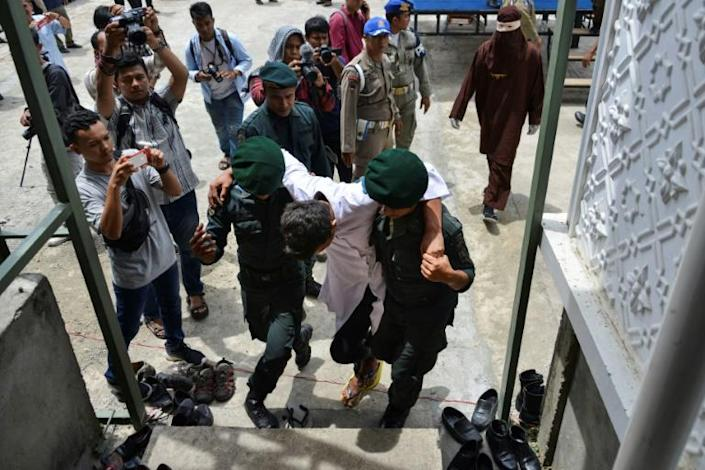 A man is carried away by religious police after being flogged in Banda Aceh in Indonesia (AFP Photo/CHAIDEER MAHYUDDIN)