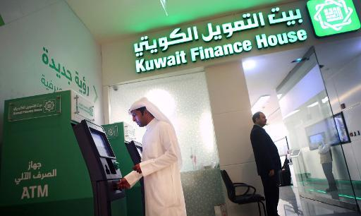 A Kuwaiti man withdraws cash from an ATM outside a Kuwait Finance House branch inside the Avenues Mall, the largest shopping centre in Kuwait on November 19, 2014