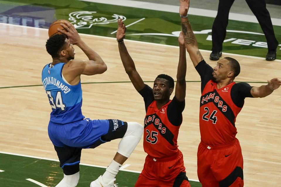 Milwaukee Bucks' Giannis Antetokounmpo shoots over Toronto Raptors' Chris Boucher (25) and Norman Powell (24) during the first half of an NBA basketball game Thursday, Feb. 18, 2021, in Milwaukee. (AP Photo/Morry Gash)