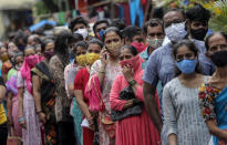 People line up to get inoculated against the coronavirus at a vaccination camp organized by the Reliance Foundation and Municipal Corporation of Greater Mumbai in Mumbai, India, Monday, Aug. 2, 2021. (AP Photo/Rajanish Kakade)