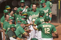 The Oakland Athletics dugout celebrates after Marcus Semien, second from right, hit a two-run home run that scored Sean Murphy (12) during the second inning of Game 2 of an American League wild-card baseball series against the Chicago White Sox, Wednesday, Sept. 30, 2020, in Oakland, Calif. (AP Photo/Eric Risberg)