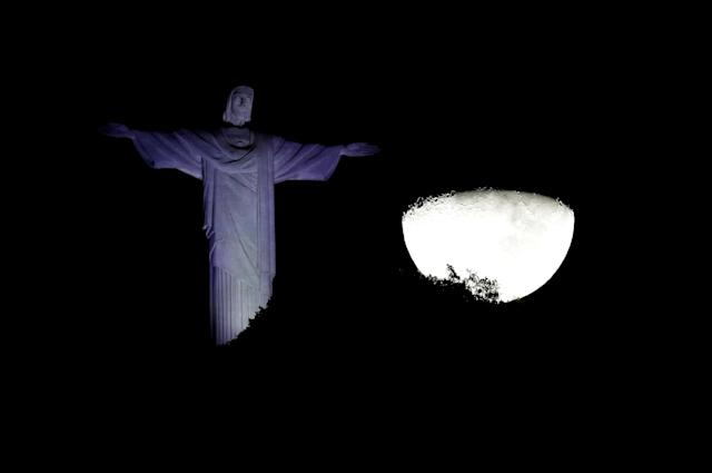 The moon is seen next to the Christ the Redeemer statue in Rio de Janeiro, Brazil June 21, 2018. Picture taken June 21, 2018. REUTERS/Bruno Kelly TPX IMAGES OF THE DAY