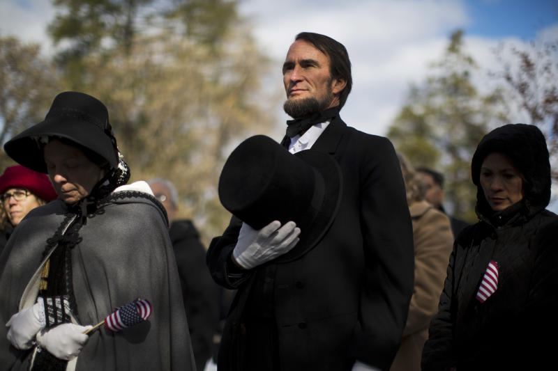 John Voehl portraying President Abraham Lincoln, covers his hart during a ceremony commemorating the 150th anniversary of the dedication of the Soldiers' National Cemetery and President Abraham Lincoln's Gettysburg Address, Tuesday, Nov. 19, 2013, in Gettysburg, Pa. Lincoln's speech was first delivered in Gettysburg nearly five months after the major battle that left tens of thousands of men wounded, dead or missing. (AP Photo/Matt Rourke)
