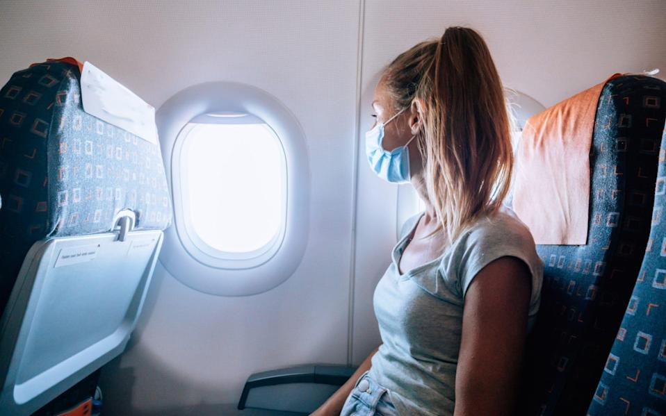 woman on plane in mask