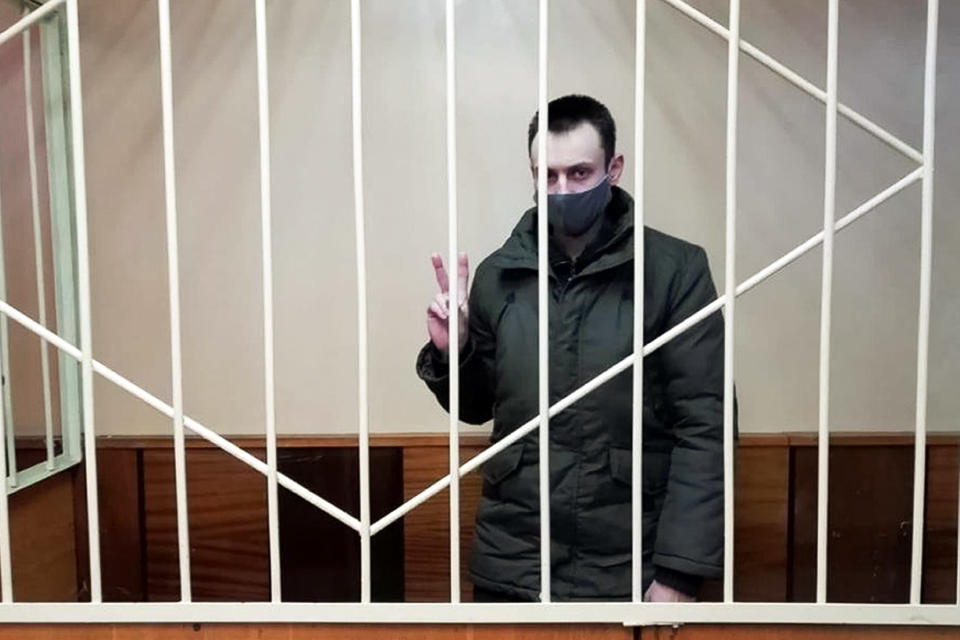 In this handout photo released by spring96.org web portal, Uladzislau Makavetsky gestures as he listens for a verdict in a courtroom in Vitebsk, Belarus, Wednesday, Dec. 16, 2020. The 28-year-old woodcarver Uladzislau Makavetsky was convicted in December of threatening a police officer with a truncheon during a clash between protesters and police in his hometown of Vitebsk and sentenced to two years in prison. He insisted that he was trying to protect an elderly man who was beaten by police and just threw away a truncheon dropped by one of the officers. Political prisoners in Belarus are coming under increasing pressure following the recent arrest of activist Raman Pratasevich from a forcibly diverted Ryanair flight. (AP Photo)
