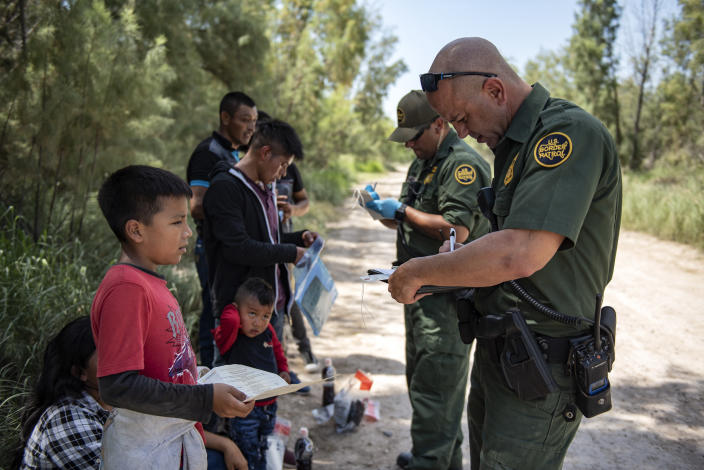 Border Patrol agents collect information from detained illegal immigrants south of McAllen, Texas. (Photo: Sergio Flores for Yahoo News)