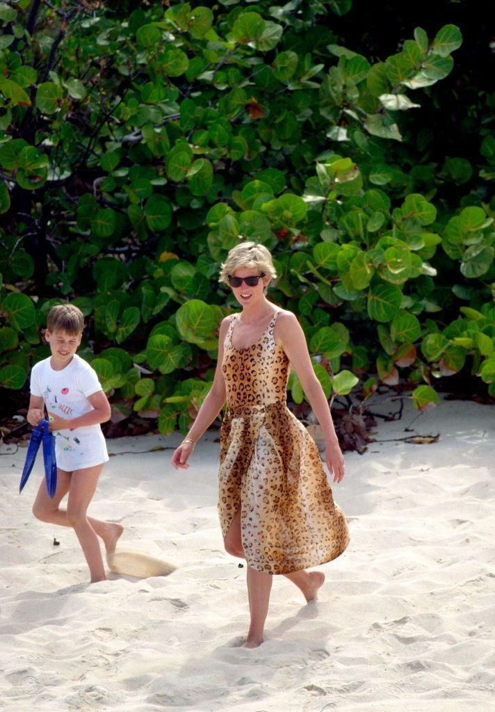 """<p>Princess Diana embodied <a href=""""https://www.townandcountrymag.com/style/fashion-trends/a32620024/beach-outfits/"""" rel=""""nofollow noopener"""" target=""""_blank"""" data-ylk=""""slk:beachside glamour"""" class=""""link rapid-noclick-resp"""">beachside glamour</a> in a matching <a href=""""https://www.townandcountrymag.com/style/fashion-trends/g36720519/one-piece-swimsuit-outfits/"""" rel=""""nofollow noopener"""" target=""""_blank"""" data-ylk=""""slk:one piece"""" class=""""link rapid-noclick-resp"""">one piece</a> and cover-up while enjoying a beach day with her sons along the shores of Necker Island.<br></p>"""