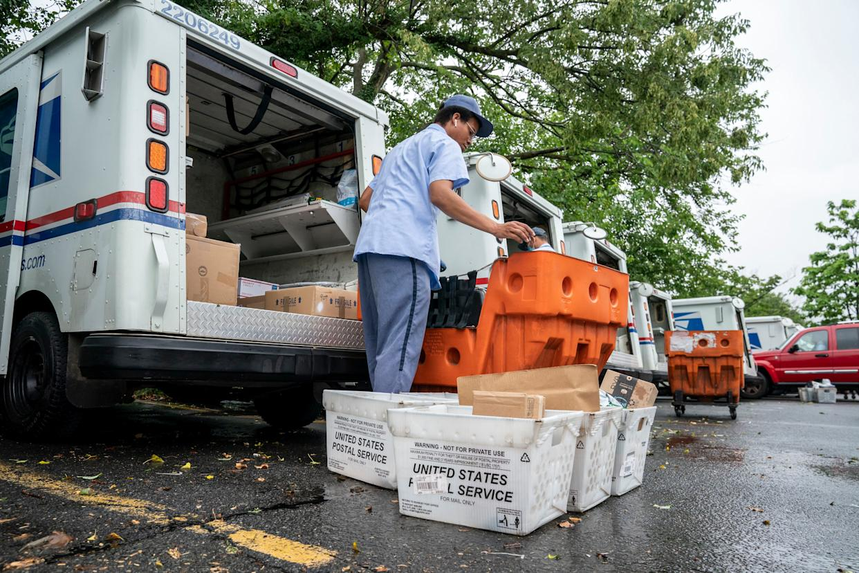 Letter carriers load mail trucks for deliveries at a U.S. Postal Service facility in McLean, Va., Friday, July 31. Delays caused by an increase in voting by mail may contribute to public doubts about the results.