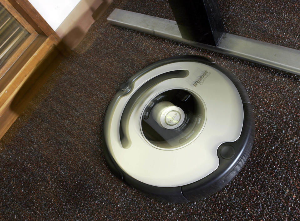 The Roomba vacuum cleaner by iRobot Corp. moves to clean an office carpet in Boston on Tuesday, Aug. 21, 2007. Nearly five years after rolling onto the market, the Roomba vacuum cleaner has undergone a ground-up redesign that has endowed the otherwise-brainy robot with the smarts to overcome rug tassels and electrical cords. (AP Photo/Elise Amendola)