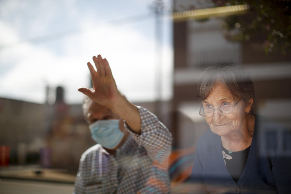 Arceli Armando watches her son wave to her from outside of the Reminiscencias residence for the elderly where she lives in Tandil, Argentina, Monday, April 5, 2021. Residents here do not have physical contact with their families or leave the residence due to the COVID-19 pandemic, but stay active with group activities within the facility. (AP Photo/Natacha Pisarenko)