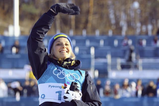 Cross-Country Skiing - Pyeongchang 2018 Winter Olympics - Women's 30km Mass Start Classic - Alpensia Cross-Country Skiing Centre - Pyeongchang, South Korea - February 25, 2018 - Bronze medallist Stina Nilsson of Sweden waves as she holds Soohorang Olympic plush mascot during flower ceremony. REUTERS/Carlos Barria