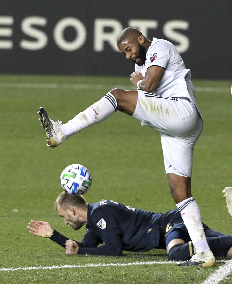 Philadelphia Union's Kacper Przybylko, bottom, and New England Revolution's Andrew Farrell collide while going after the ball during the second half of an MLS soccer playoff match Tuesday, Nov. 24, 2020, in Chester, Pa. (Charles Fox/The Philadelphia Inquirer via AP)