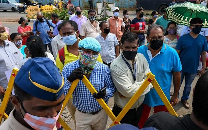 People stood behind a barrier at a Mumbai vaccination centre where appointments were suspended - Punit Paranjpe/AFP