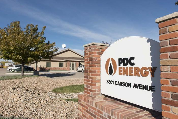 Sign reading PDC Energy in front of a small office building and rock landscaping.