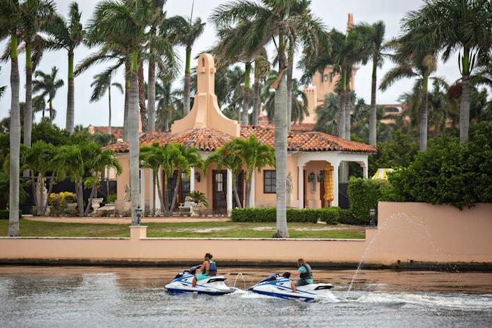 People on Jet Skis pass Mar-a-Lago in Palm Beach.