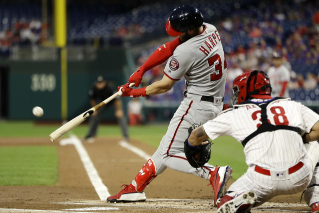 Washington Nationals' Bryce Harper, left, hits a two-run home run off Philadelphia Phillies starting pitcher Aaron Nola during the first inning of a baseball game, Wednesday, Sept. 12, 2018, in Philadelphia. At right is catcher Jorge Alfaro. (AP Photo/Matt Slocum)