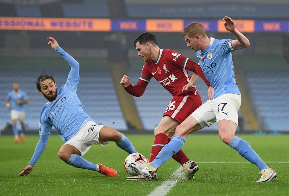 Liverpool's Andrew Robertson (centre) in action with Manchester City's Bernardo Silva (left) and Kevin de Bruyne.