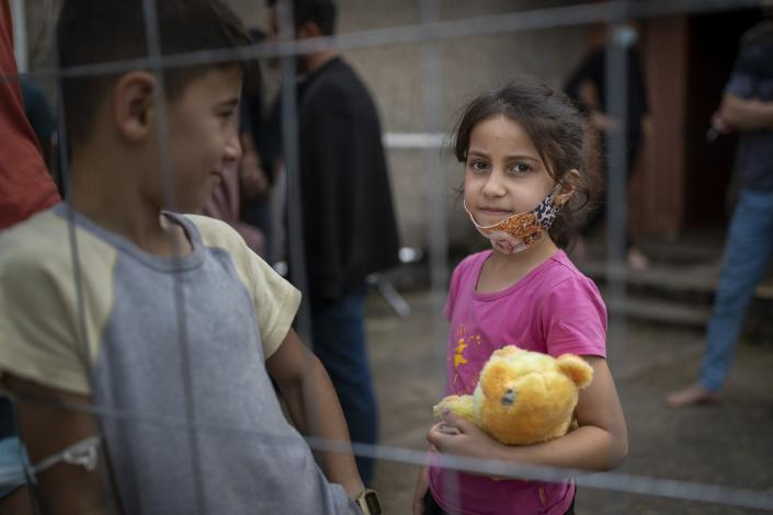 Girl, a migrant from Iraq, looks through a fence at the refugee camp in the village of Verebiejai, some 145km (99,1 miles) south from Vilnius, Lithuania, Sunday, July 11, 2021. Migrants at the school in the village of Verebiejai, about 140 kilometers (87 miles) from Vilnius, haven't been allowed to leave the premises and are under close police surveillance. Some have tested positive for COVID-19 and have been isolated in the building. (AP Photo/Mindaugas Kulbis)