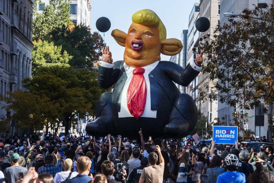 A ballon depicting a caricature of Donald Trump is carried by revelers in Washington, D.C. to celebrate Joe Biden becoming the 46th president of the United States. (Photo By Tom Williams/CQ Roll Call)