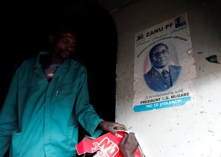 A man walks past a portrait of late former Zimbabwe's President Robert Mugabe, at a groceries store in Mbare township, Harare