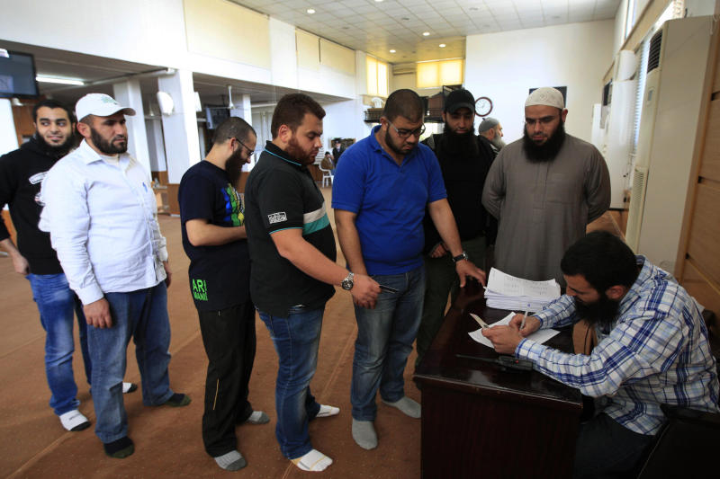 Lebanese Sunni Muslim men queue as they register their names for jihad in Syria, at a mosque in the southern port city of Sidon, Lebanon, Tuesday, April 23, 2013. Lebanese Sunni Muslim clerics Ahmad Al-Assir and Sheikh Salem al-Rafie called late Monday for jihad in Syria to protect Sunnis in villages under attack by Syrian troops and pro-government Shiite gunmen. Lebanon and Syria share a complex web of political and sectarian ties and rivalries which are easily enflamed. Lebanon, a country plagued by decades of strife, has been on edge since the uprising in Syria against President Bashar Assad began in March 2011, with deadly clashes between pro and anti- Assad Lebanese groups erupting on several occasions. (AP Photo/Mohammed Zaatari)