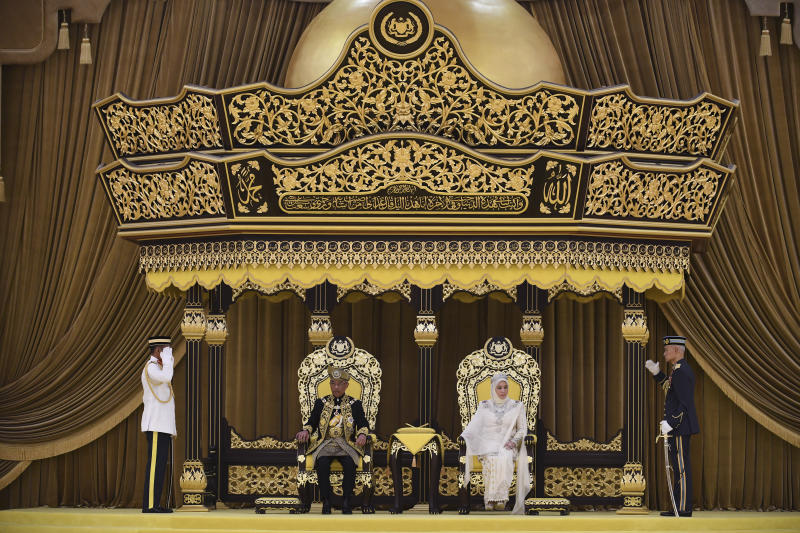 In this photo released by Malaysia's Department of Information, Malaysia's King Sultan Abdullah Sultan Ahmad Shah, center left, and Queen Tunku Azizah attend the royal coronation at the National Palace in Kuala Lumpur Tuesday, July 30, 2019. Malaysia's new king called for racial unity as he was formally installed as the country's 16th king under a unique rotating monarchy system. (Malaysia Information Ministry via AP)