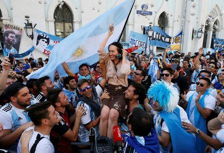 Supporters of the Argentine national soccer team, a participant of the soccer World Cup, lift a journalist during a gathering in central Moscow, Russia June 15, 2018. REUTERS/Gleb Garanich