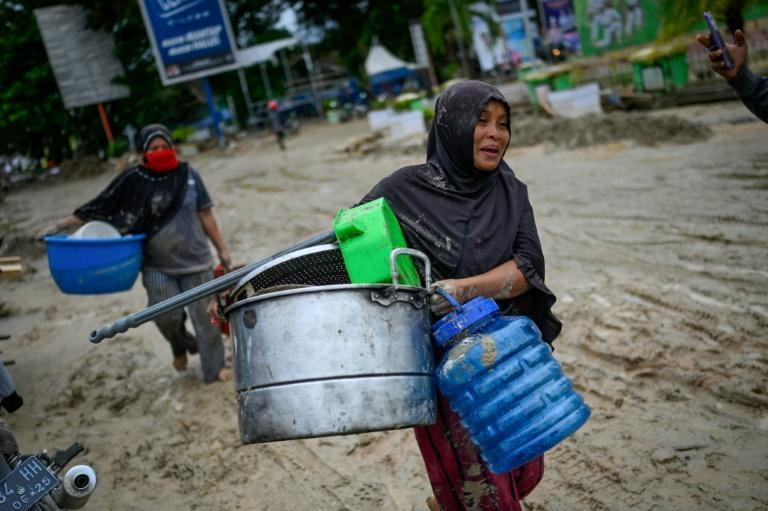 Villagers salvage belongings from their homes as they head to evacuation shelters to take refuge after flash floods left hundreds of houses buried in mud in South Sulawesi