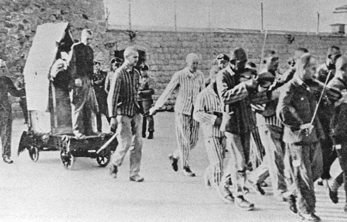"""<span class=""""caption"""">Prisoners are forced to play music as they lead a fellow prisoner to his execution at the Mauthausen concentration camp in Austria.</span> <span class=""""attribution""""><a class=""""link rapid-noclick-resp"""" href=""""https://www.gettyimages.com/detail/news-photo/prisoners-are-forced-to-give-company-to-fellow-sufferers-news-photo/503021537?adppopup=true"""" rel=""""nofollow noopener"""" target=""""_blank"""" data-ylk=""""slk:Votava/Imagno via Getty Images"""">Votava/Imagno via Getty Images</a></span>"""