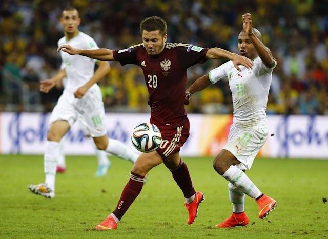 Russia's Victor Faizulin (20) fights for the ball with Algeria's Yacine Brahimi during their 2014 World Cup Group H soccer match at the Baixada arena in Curitiba June 26, 2014. REUTERS/Damir Sagolj (BRAZIL - Tags: SOCCER SPORT WORLD CUP)