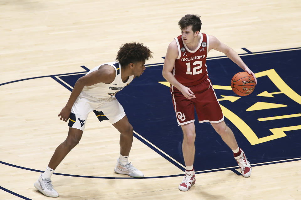 Oklahoma guard Austin Reaves (12) is defended by West Virginia guard Miles McBride (4) during the second half of an NCAA college basketball game Saturday, Feb. 13, 2021, in Morgantown, W.Va. (AP Photo/Kathleen Batten)