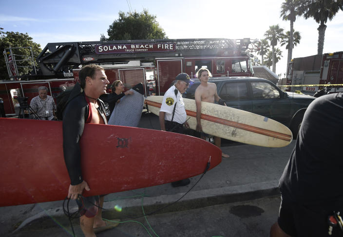Surfers wait at the top of the stairs above the site of a cliff collapse at a popular beach Friday, Aug. 2, 2019, in Encinitas, Calif. At least one person was reportedly killed, and multiple people were injured, when an oceanfront bluff collapsed Friday at Grandview Beach in the Leucadia area of Encinitas, authorities said. (AP Photo/Denis Poroy)