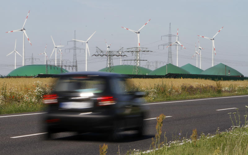 """FILE - In this June 29, 2011 file photo a car passes by a a biogas plant and windmills near Nauen, Germany. The crisis in Ukraine is underlining the urgency of Germany's biggest political challenge as Chancellor Angela Merkel's new government marks 100 days in office Wednesday, March 26, 2014, getting the country's mammoth transition from nuclear to renewable energy sources on track. The transition started in earnest when Merkel, after Japan's 2011 Fukushima nuclear disaster, abruptly accelerated Germany's exit from nuclear power. Since then, the """"Energiewende"""" _ roughly, """"energy turnaround"""" _ has created increasing headaches. (AP Photo/Ferdinand Ostrop, File)"""