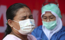 A woman receives the AstraZeneca vaccine during a mass coronavirus vaccination for public transport workers at the Kampung Rambutan Bus Terminal in Jakarta, Indonesia, Thursday, June 10, 2021. (AP Photo/Achmad Ibrahim)