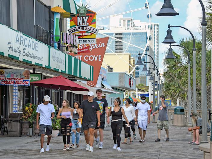 Pedestrians, some wearing masks, on the boardwalk in Myrtle Beach, S.C., on Monday, June 29, 2020. (Tanya Ackerman/The New York Times)