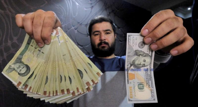Money changer poses for the camera with U.S hundred dollar bill and the amount being given when converting it into Iranian rials, at a currency exchange shop in Tehran's business district, Iran