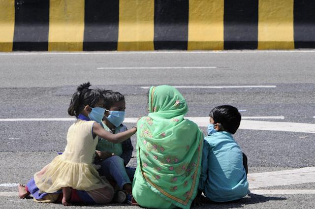 NOIDA, INDIA - MARCH 29: A migrant worker with children headed back home pauses for break, on day 5 of the nationwide lockdown imposed by PM Narendra Modi to check the spread of coronavirus, at Yamuna expressway zero point, on March 29, 2020 in Noida, India. (Photo by Sunil Ghosh /Hindustan Times via Getty Images)