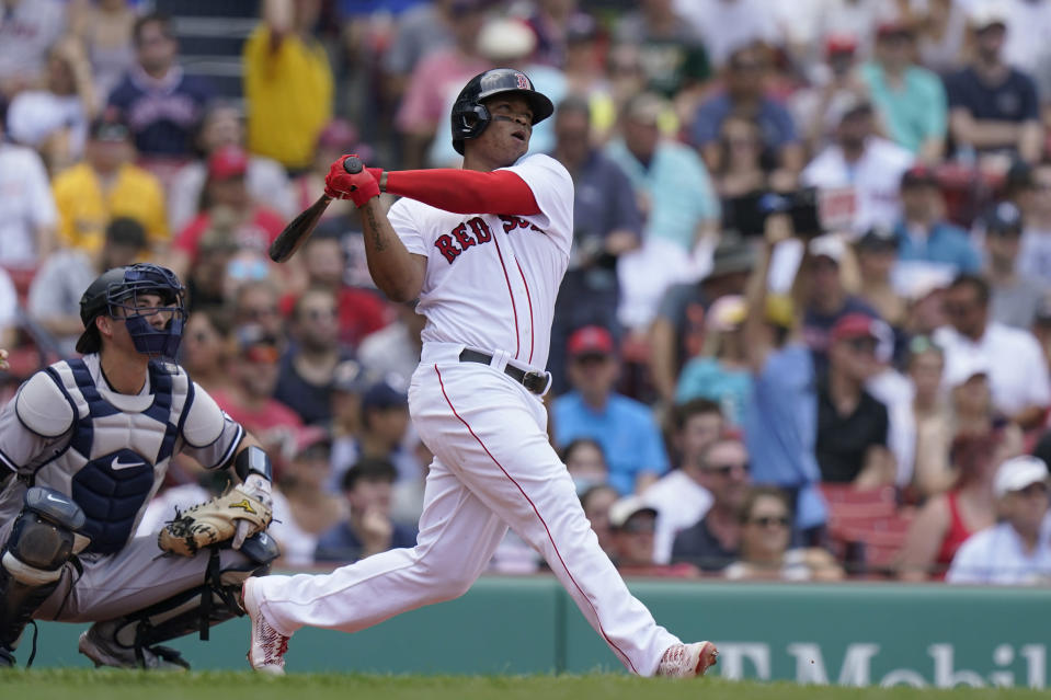 Boston Red Sox's Rafael Devers, right, hits a three-run home run as New York Yankees catcher Kyle Higashioka, left, looks on in the first inning of a baseball game, Sunday, June 27, 2021, in Boston. (AP Photo/Steven Senne)