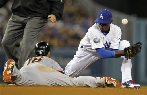 Los Angeles Dodgers shortstop Dee Gordon can't get the handle on the ball as San Francisco Giants' Angel Pagan takes second base in the fifth inning of a baseball game in Los Angeles Monday, May 7, 2012. Gordon had two errors on the play. (AP Photo/Reed Saxon)