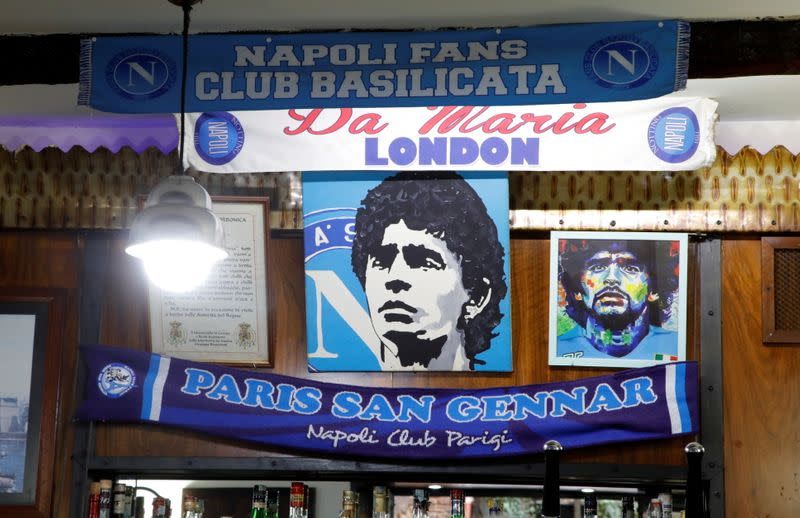 Posters depicting late soccer legend Diego Maradona are pictured the day after his death in Naples
