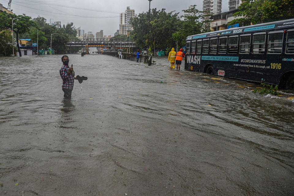 A commuter steadies himself to negotiate flowing water while crossing a flooded road during a heavy monsoon rain in Mumbai on August 4, 2020.(Photo by INDRANIL MUKHERJEE/AFP via Getty Images)
