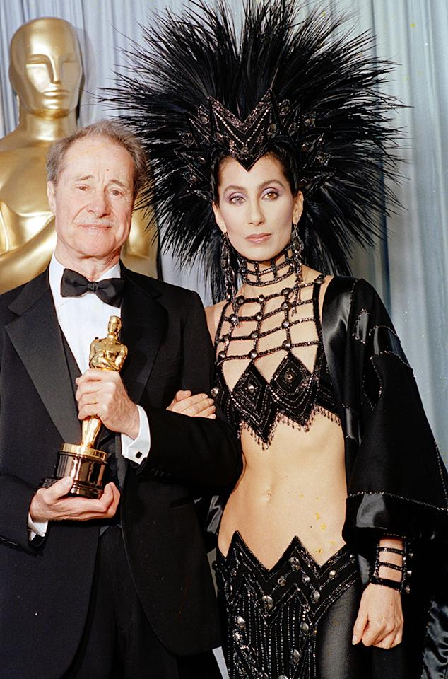 "Cher, 1986. Cher certainly set the bar for preposterous in Bob Mackie. The showgirl flamboyance, though, was an in-your-face gesture to the academy after she was egregiously snubbed for her performance in ""Mask."" She had been told, ""the academy doesn't think you're serious, [when] you don't dress seriously,"" so what other recourse did the singer-actress have except to supersize burlesque?"