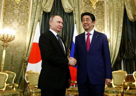 Russian President Vladimir Putin shakes hands with Japanese Prime Minister Shinzo Abe during a meeting at the Kremlin in Moscow, Russia April 27, 2017. REUTERS/Sergei Karpukhin