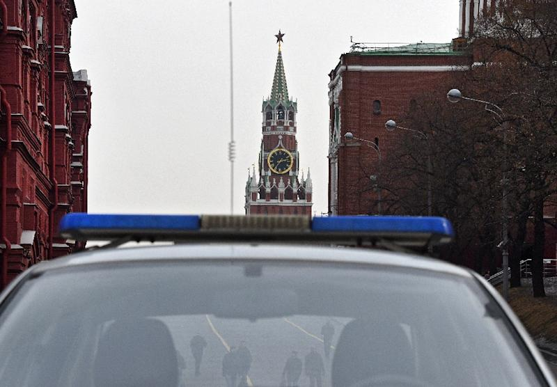 A group of men pictured through a police car window in central Moscow, with the Kremlin's Spasskaya (Saviour) Tower seen in the background, on March 1, 2017