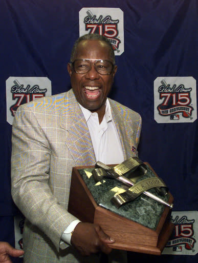 """FILE - In this April 8, 1999, file photo, Major League Baseball's all-time career home run record holder Hank Aaron laughs as he shows off the newly unveiled """"Hank Aaron Award"""" during a news conference in Atlanta. Hank Aaron, who endured racist threats with stoic dignity during his pursuit of Babe Ruths home run record and gracefully left his mark as one of baseballs greatest all-around players, died Friday. He was 86. The Atlanta Braves, Aaron's longtime team, said he died peacefully in his sleep. No cause was given. (AP Photo/John Bazemore, File)"""