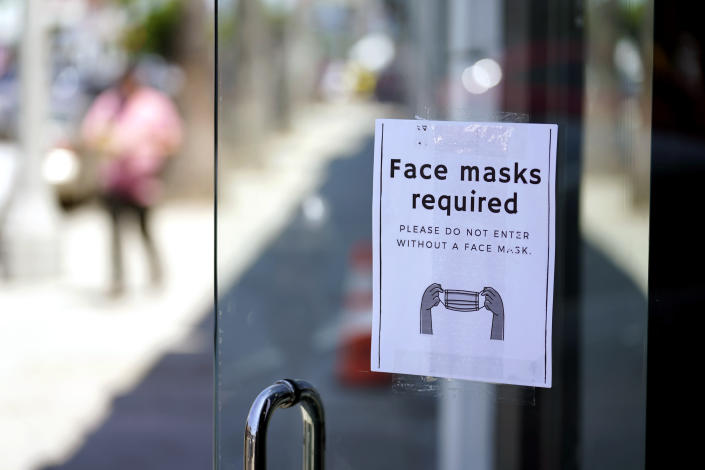 FILE - A sign advises shoppers to wear masks outside of a store Monday, July 19, 2021, in the Fairfax district of Los Angeles. Infections are climbing across the U.S. and mask mandates and other COVID-19 prevention measures are making a comeback in some places as health officials issue increasingly dire warnings about the highly contagious delta variant. But in a possible sign that the warnings are getting through to more Americans, vaccination rates are creeping up again, offering hope that the nation could yet break free of the coronavirus if people who have been reluctant to receive the shot are finally inoculated. (AP Photo/Marcio Jose Sanchez, File)