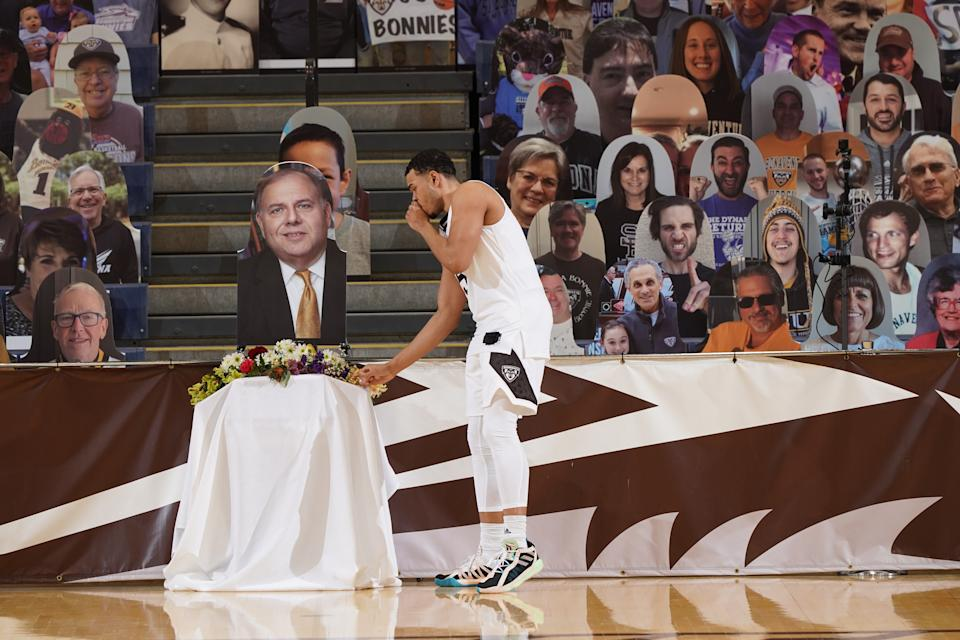 St. Bonaventure's Jaren Holmes lays flowers on a cutout of Dennis R. DePerro before a game against Dayton on March 1. (Photo courtesy of St. Bonaventure athletics)