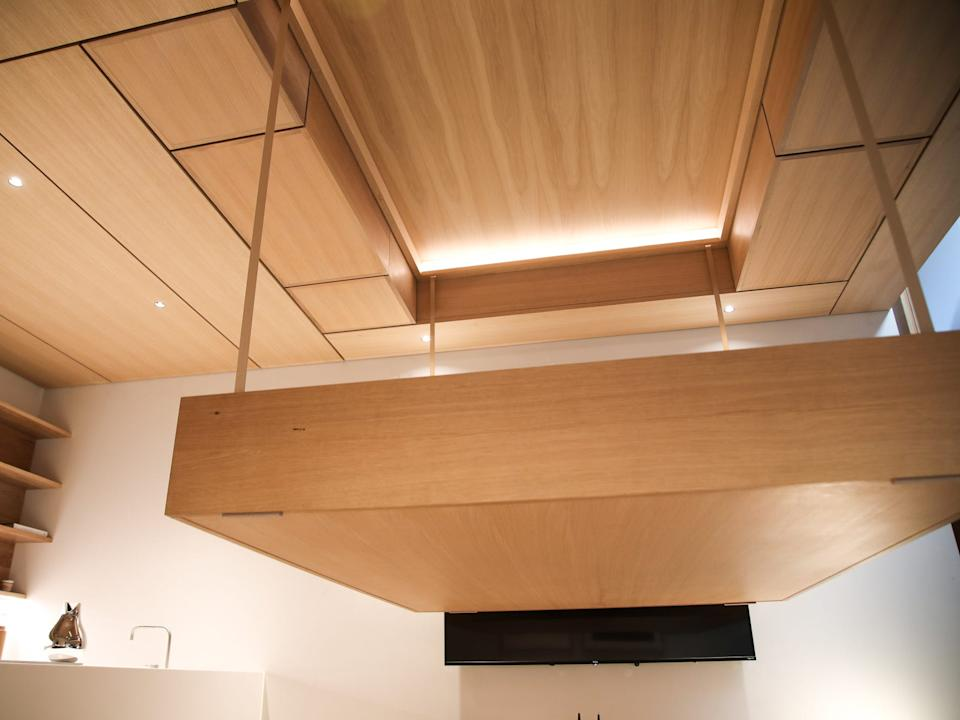 A bed is seen lowering from the ceiling in a demo space.