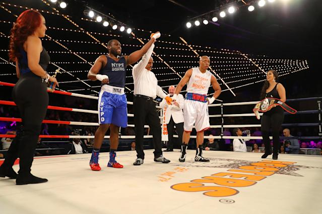 <p>Emmanuel Etienne's (red) arm is raised after hearing the decison from the judges after he and David Thompson (blue) battled in the ring during a Heavyweight bout in the NYPD Boxing Championships at the Hulu Theater at Madison Square Garden on March 15, 2018. (Gordon Donovan/Yahoo News) </p>