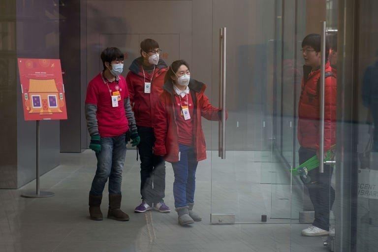Shop assistants wear face masks as they welcome customers at a store in Beijing, January 29, 2013. Beijing authorities have stepped up their health warnings to residents as thick smog blanketed the Chinese capital and large swathes of the country for a third consecutive day